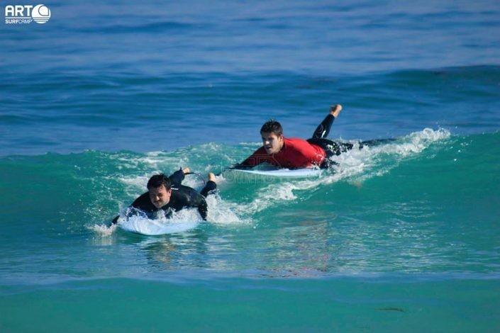 Monitor con alumno de surf
